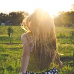 moteris-plaukai-pieva-saule